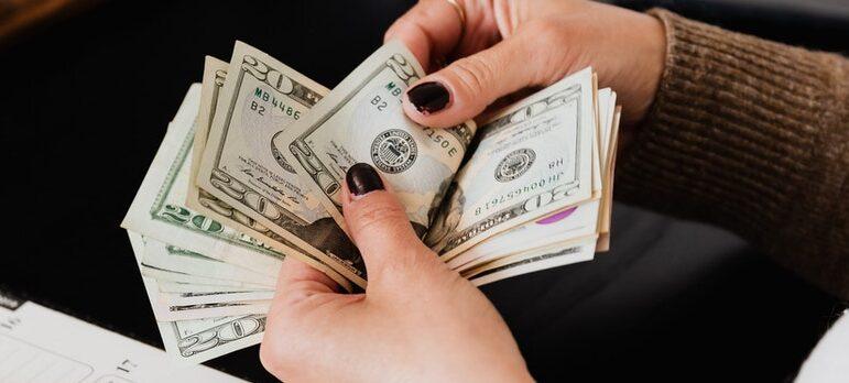 A woman counting dollar bills