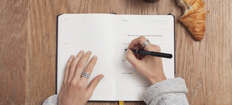 Woman writing in a planner to prepare for moving from Montana to California