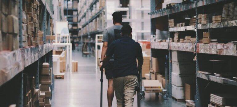 Two people looking for something in a warehouse with boxes.