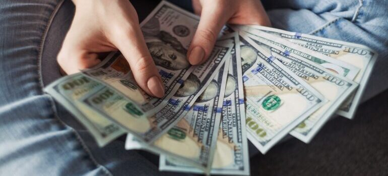 A woman holding money, saved after hiring the best cross country movers Seattle has.