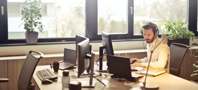 A man talking on a headset in an office.