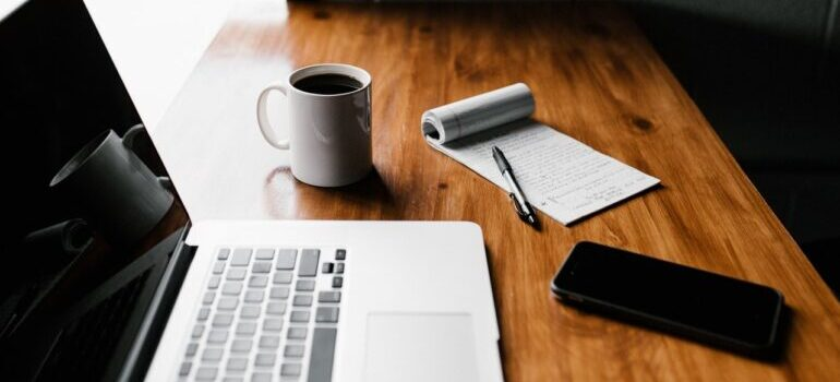 A laptop next to a pen and paper, a cup of coffee, and a smartphone.