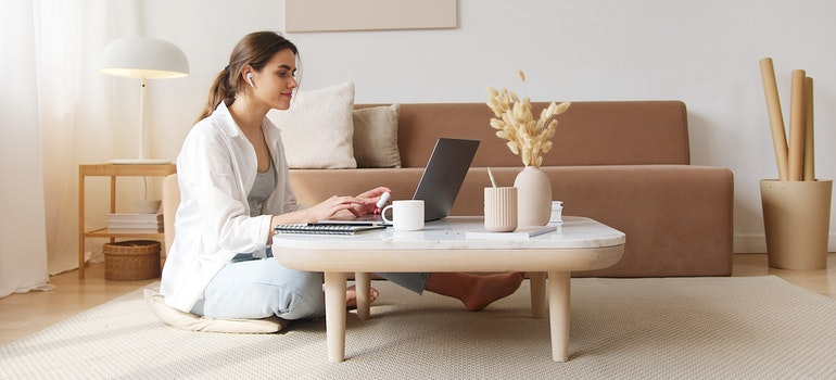 A woman sitting on the floor and using a laptop