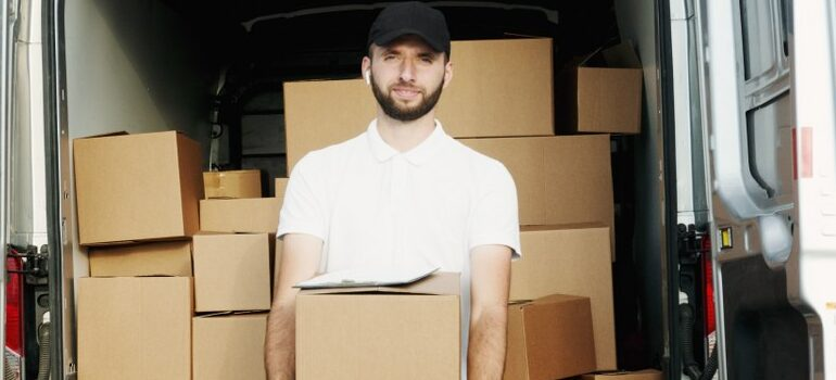 male in a black hat and white shirt holding a box