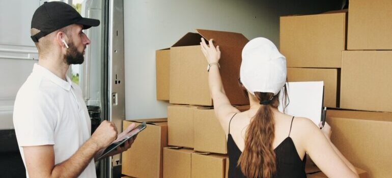 A man and a woman with caps looking at cardboard boxes.