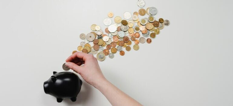 A woman putting money in a black piggy bank against a white background.