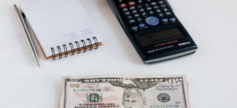 money, calculator, notebook on the table