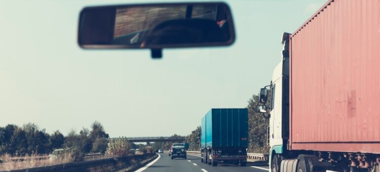 A moving truck on a highway seen from a windshield of a car.