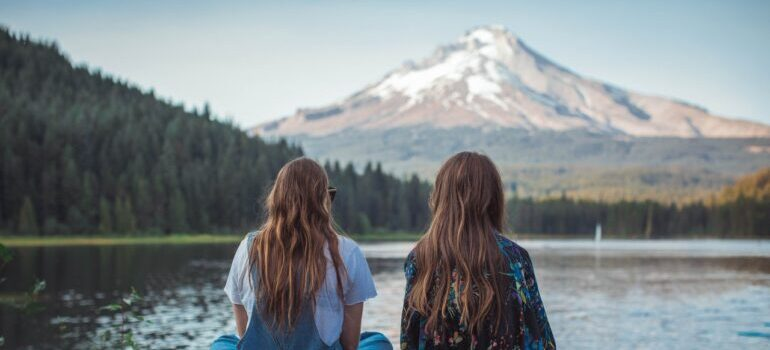 Two girls looking over a lake in Oregon, after hiring the best cross country movers Salem has to move them there.