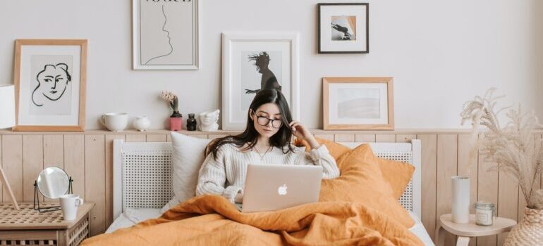 A woman browsing on her laptop in her bed.