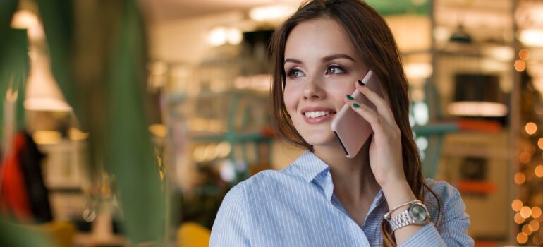 A woman smiling while talking on the phone.