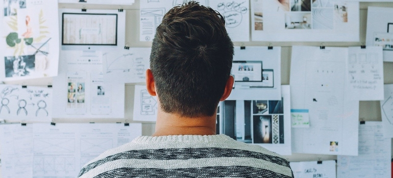 A man looking up at a whiteboard with complicated plans.