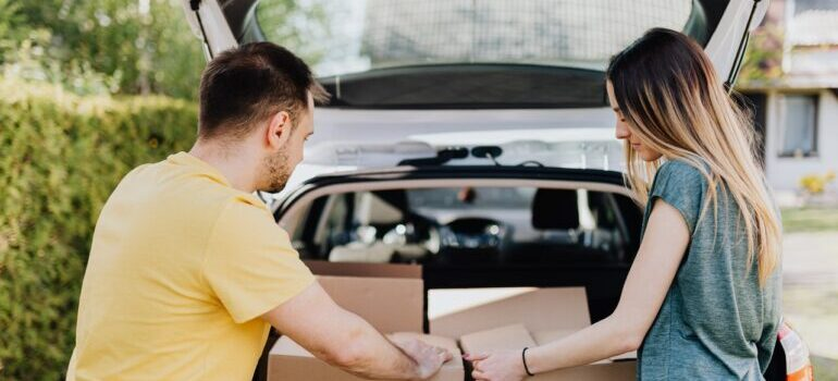 two people loading boxes into a car