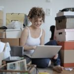 woman sitting on the floor among boxes working on a computer trying to evaluate cross country moving companies