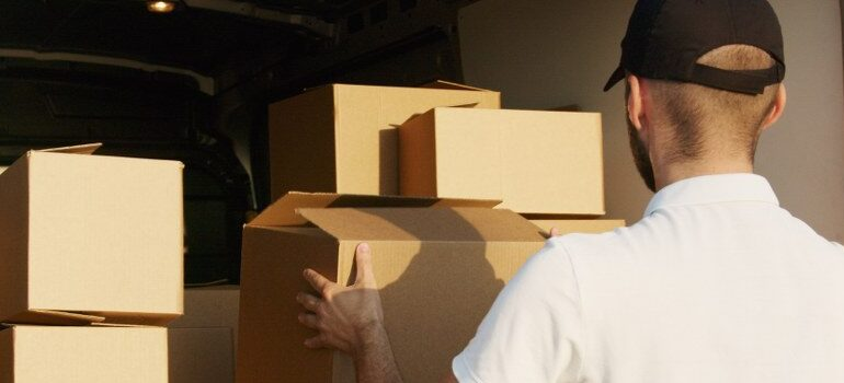 male in a white shirt and black hat loading a van