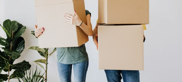 two people holding cardboard moving boxes
