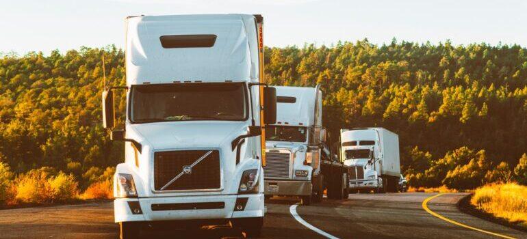 A row of trucks going along a highway.