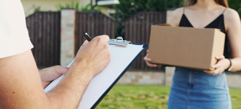 A man holding a clipboard next to woman with a box, as she hires the best cross country movers in Rockville.