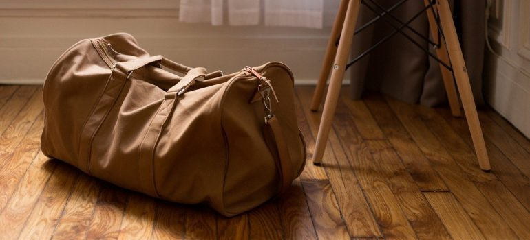 A brown travel bag on a wooden floor.