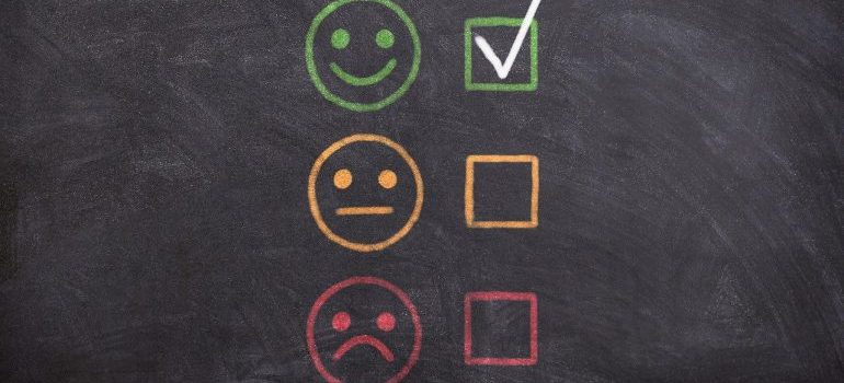 A blackboard containing three emojis depicting different emotions, and checkboxes next to them.