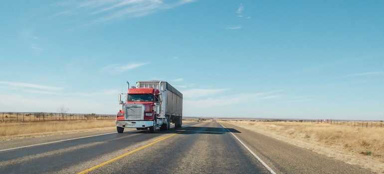A truck on a desert road, depicting the best cross country movers in Rochester.