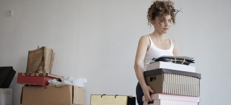A woman carrying stacks of items next to boxes.