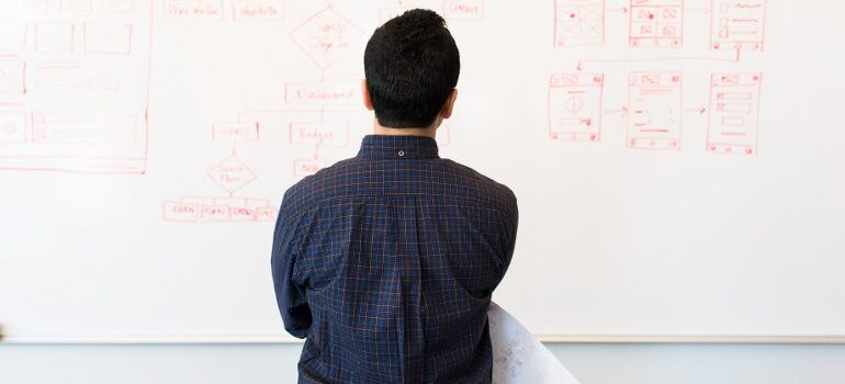person standing in front of a white board