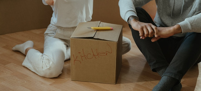 Couple sitting next to a carton box