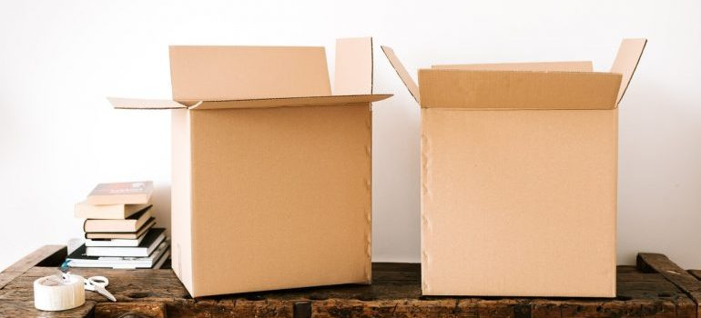 Two boxes made out of cardboard sitting on a wooden desk.