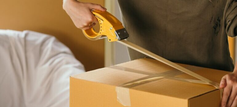 best cross country movers Great Falls applying packing tape on a cardboard box.