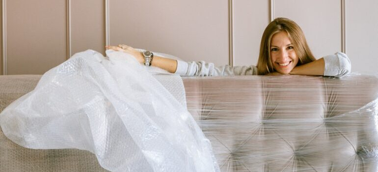 A woman wrapping her couch in see-through tape.