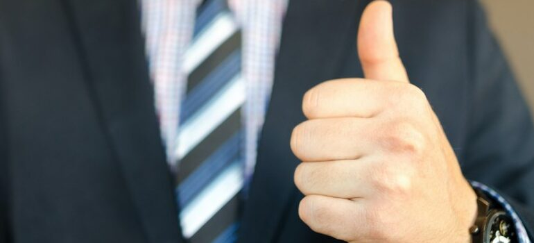 male in a suit, thumbs up