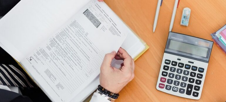 businessman going through work papers, calculator on the table