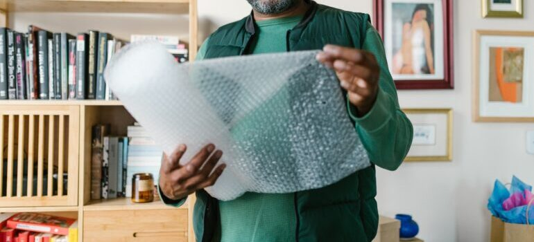 A man holding wrapping materials for packing.