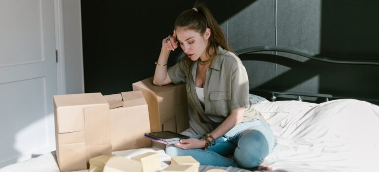 A woman sitting on the floor surrounded by packing materials.
