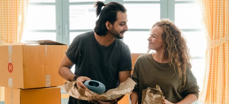 A woman and a man looking at each other while packing items in cardboard boxes.