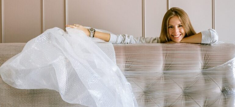 A woman laughing while wrapping her couch before a move.