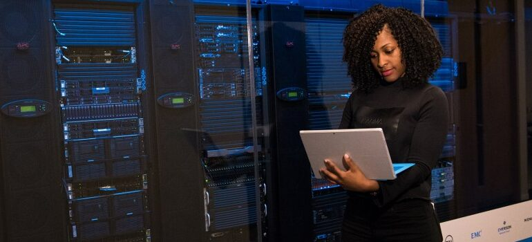 woman in a server room, working on a laptop