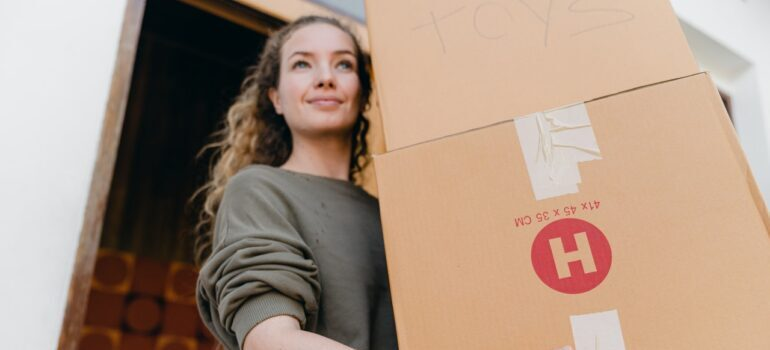 Blong woman holding two cardboard boxes for moving.