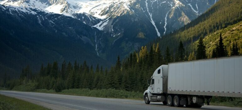 White truck on the road with mountains in the background.