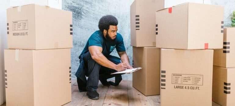 A man working as a mover in a moving companies, squatting next to bunch of cardboard boxes and writing something on the paper.