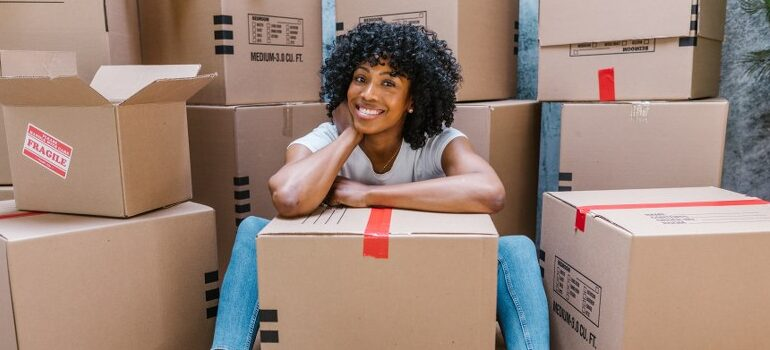 woman smiling in the midle of cardboard boxes
