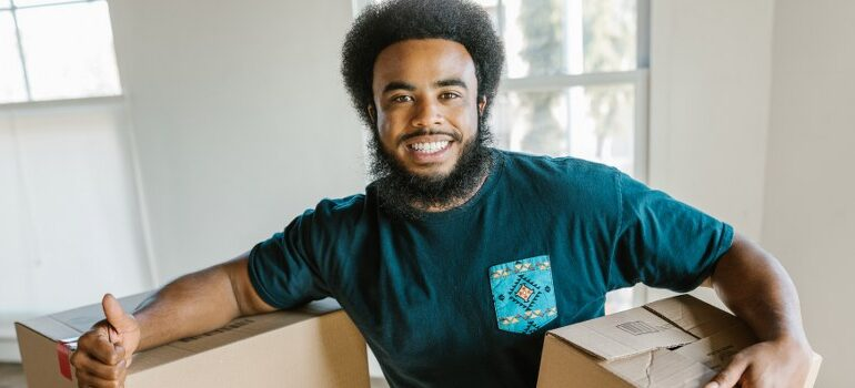 man giving a thumbs up, holding a cardboard box