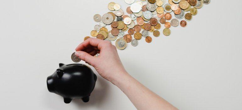 person putting a dime in a piggybank
