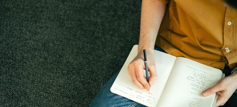 A female person sitting down and holding a notebook in her lap while writing something down.
