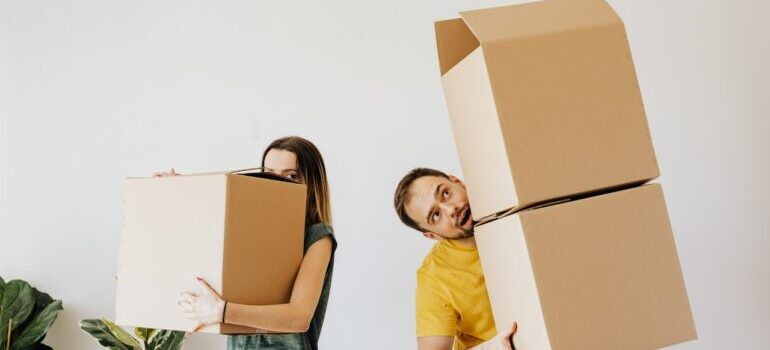 A cheerful man and a woman carrying cardboard boxes for the move.