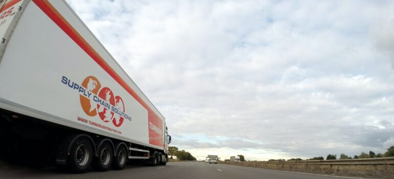 A white trailer truck in move on the road.