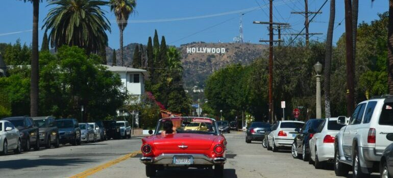 Red car on the street with the Hollywood sign on the hill.