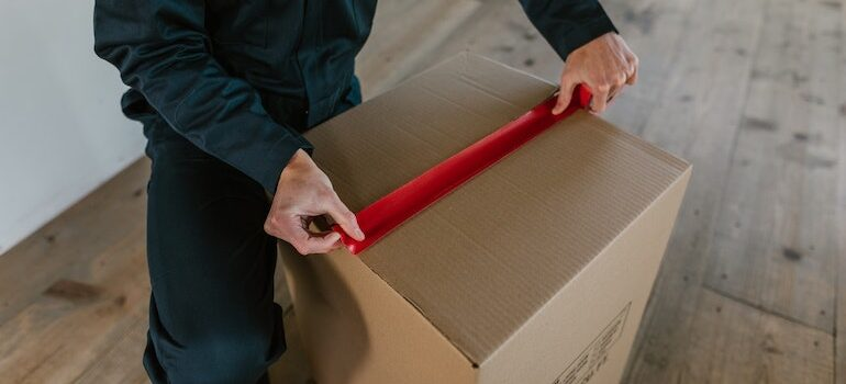 hands taping a box with duct tape