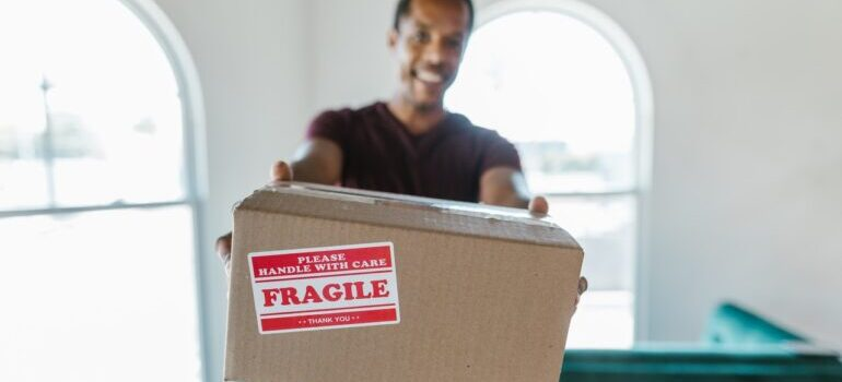 A worker holding a cardboard box with label saying that its fragile.